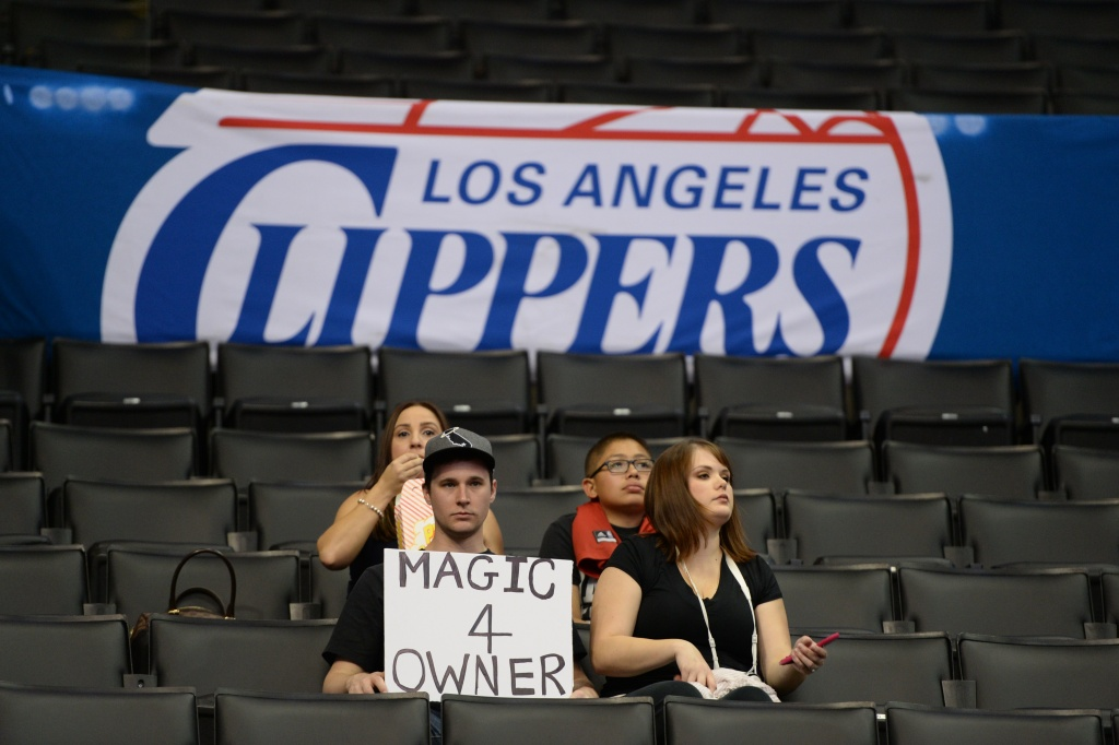 Fans holds a sign reading 'Magic 4 Owner' before the start of the NBA playoff game between the Los Angeles Clippers and the Golden State Warriors, April 29, 2014 at Staples Center in Los Angeles, California.