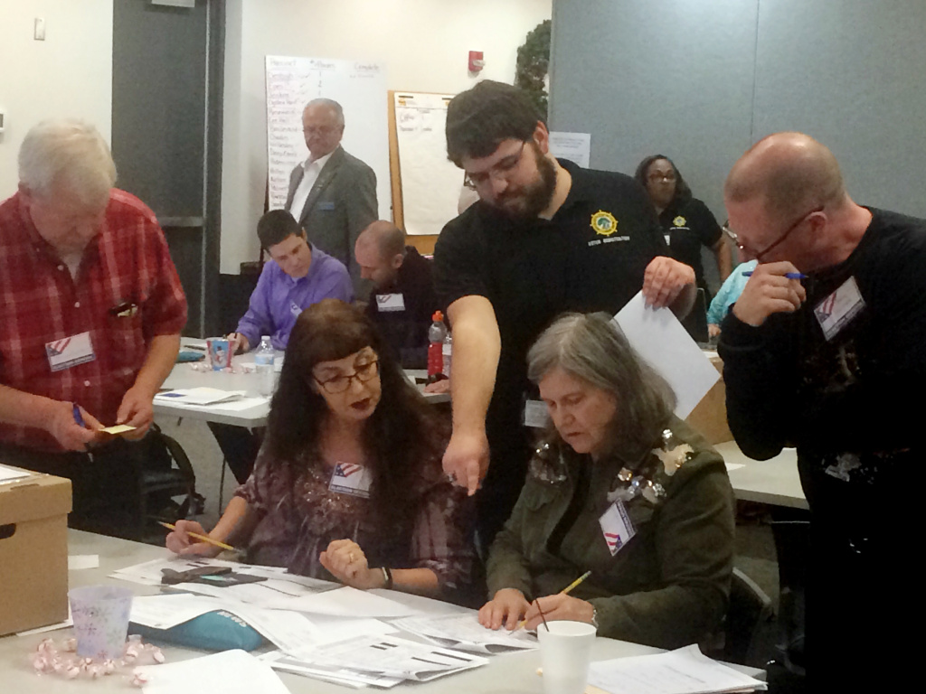 Election officials in Newport News, Va., examine ballots during a recount for a House of Delegates race on Tuesday, Dec. 19, 2017.