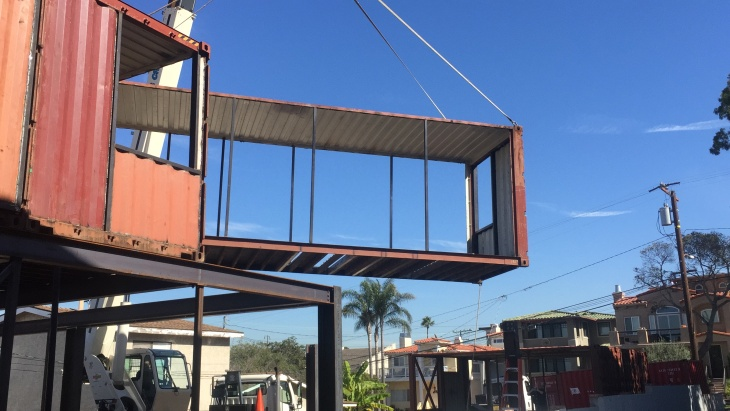 A crane positions an up-cycled shipping container into place as part of the structural construction of a sustainable home in Redondo Beach.