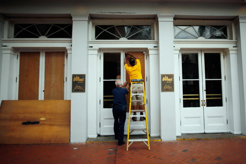 Workers place plywood on the windows of the Royal Sonesta Hotel on Bourbon St. to prepare for Tropical Storm Isaac in New Orleans, Louisiana.