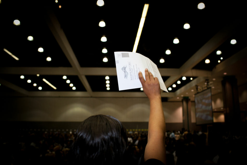 A worker holds up a voter registration form at the naturalization ceremony for 7,362 immigrants at the Los Angeles Convention Center on June 27.
