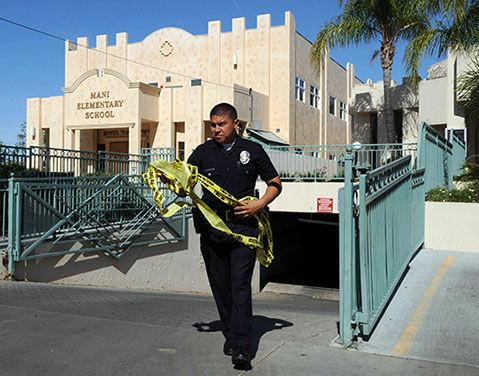 A policeman takes down crime tape.