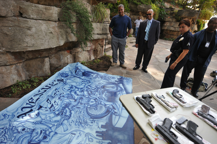 Police officers look at a large painting confiscated from a raided home of alleged Avenues gang member is on display at a press conference to announce the massive early-morning raid by hundreds of police officers and federal law enforcement agents against the notorious gang, in Los Angeles, CA on September 22, 2009.