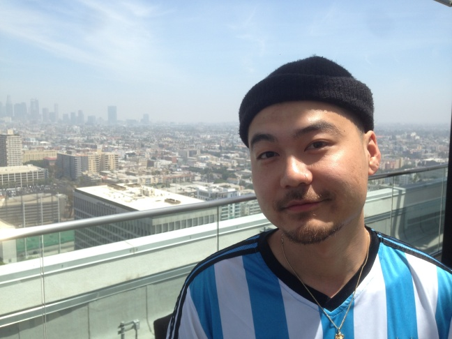 Rapper Dumbfoundead, whose real name is Jonathan Park, stands on the roof of his apartment building overlooking Koreatown