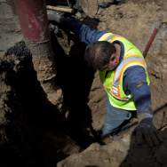 Christopher Cadena climbs in a hole five-feet deep, unearthing  a leaking water main that feeds the fire sprinkler system at Hoover Street Elementary School. A backlog of repair requests show plumbing problems plague many campuses.