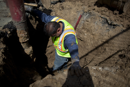 File: Christopher Cadena climbs in a hole five-feet deep, unearthing a leaking water main that feeds the fire sprinkler system at Hoover Street Elementary School. A backlog of repair requests show plumbing problems plague many campuses.