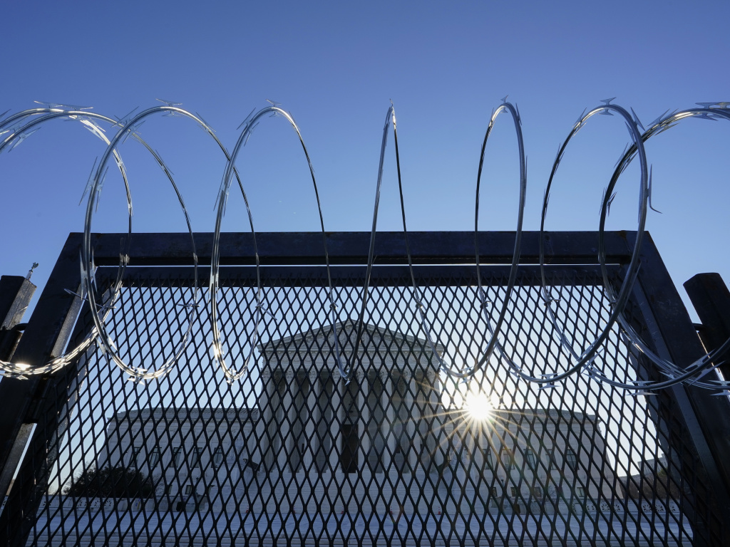 The Supreme Court is seen beyond a razor wire-topped fence at sunrise on March 8.