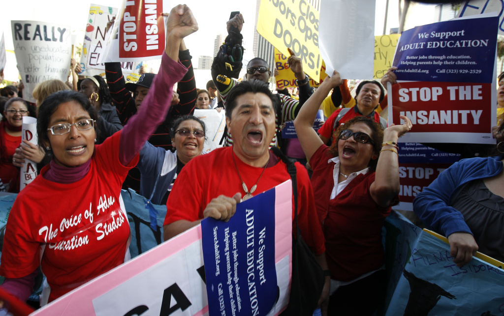 File: Teachers, parents and supporters rally as the Los Angeles Unified School District board meets to consider budget cuts and layoffs, which include adult education, preschool and elementary school arts programs, in Los Angeles on Tuesday Feb. 14, 2012.