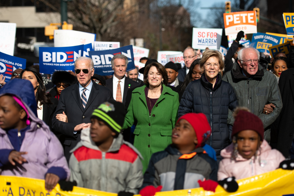 Democratic presidential candidates, former Vice President Joe Biden, left, Sen. Amy Klobuchar (D-MN), Sen. Elizabeth Warren (D-MA), and Sen. Bernie Sanders (I-VT), right, march down Main St. to the King Day at the Dome event on January 20, 2020 in Columbia, South Carolina.