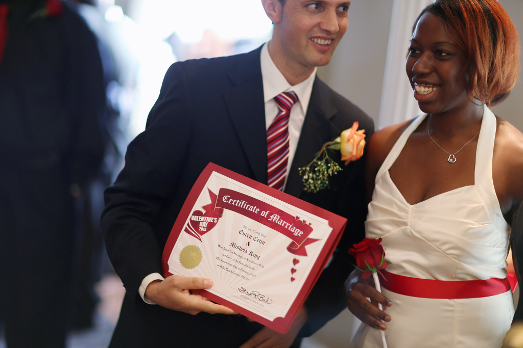 Evan Cetin and Michelle Renne (L-R) hold their marriage certificate after being wed during a group Valentine's day wedding at the National Croquet Center on February 14, 2013 in West Palm Beach, Florida.