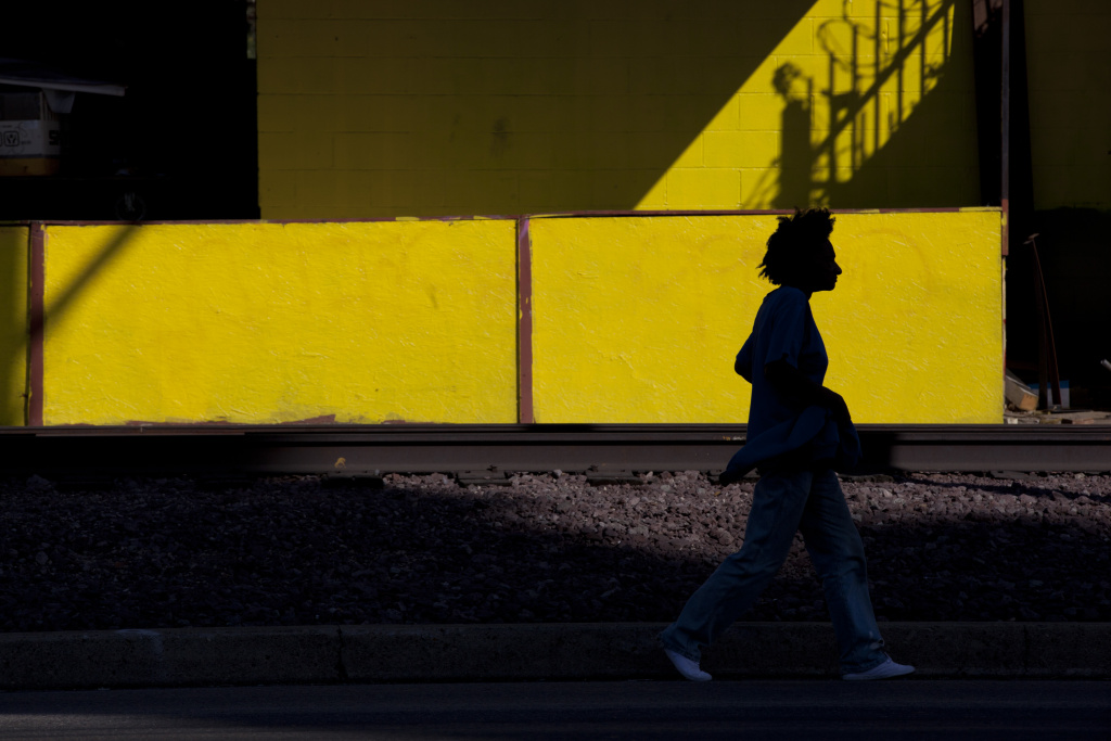 A woman walks along the train tracks on Slauson Avenue. The Metropolitan Transportation Authority is will turn the defunct tracks in a green space for pedestrians and bikers.