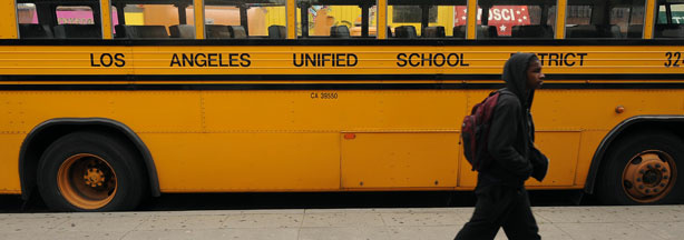 A student on his way to school walks past a Los Angeles Unified School District (LAUSD) school, in Los Angeles, California on February 13, 2009.