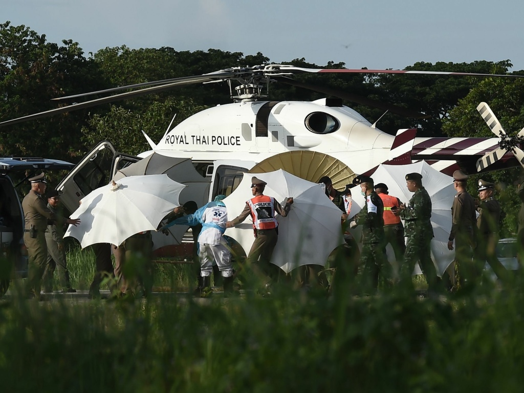 Police and military personnel use umbrellas to cover a stretcher as it is carried to a helicopter from an ambulance at a military airport in Chiang Rai, Thailand, on Monday, as rescue operations continue for those still trapped inside the cave in Khun Nam Nang Non Forest Park in the Mae Sai district.