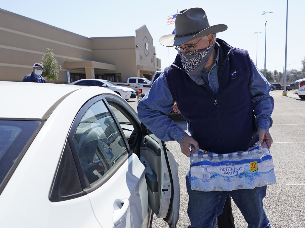 Harris County Precinct 4 Commissioner Jack Cagle hands out water at a distribution site on Friday in Houston. Millions throughout the state remain under a boil water notice as many residents lack water at home due to frozen or broken pipes.