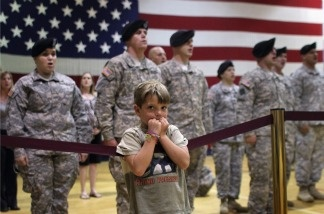 A boy stands with U.S. Army soldiers during a welcome home ceremony for troops returning from from Iraq.