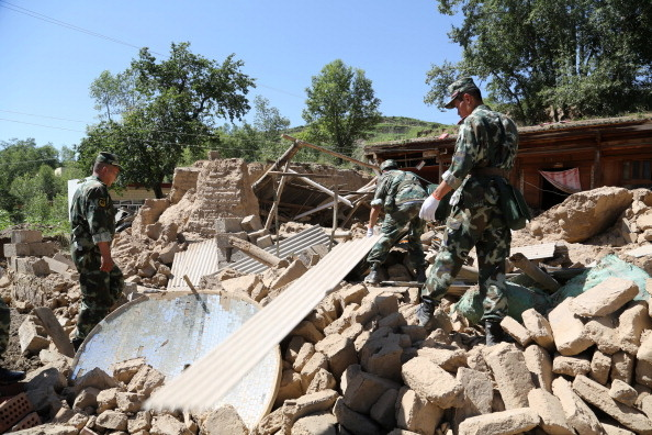 Rescuers rushed to find victims buried by twin shallow earthquakes in northwest China Monday after the double tremors killed at least 75 people and injured almost 600, officials said. (Photo: Rescuers search for survivors in the ruins of a damaged house in Hetuo township in Dingxi, northwest China's Gansu province on July 22, 2013).