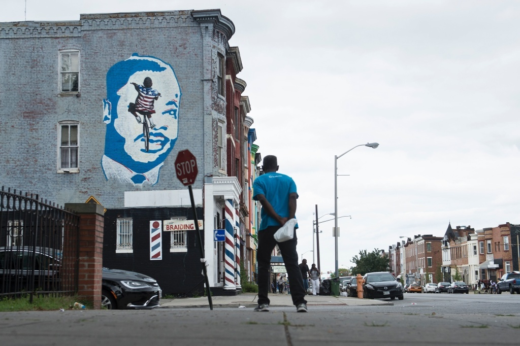 A man looks to a mural on June 23 in the area where riots broke out after the funeral for Freddie Gray last year in Baltimore.