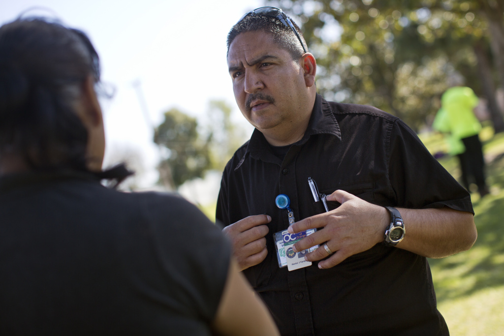 Hector Varela, a mental health clinician with Orange County, works with the Fullerton Police Department. Varela talks with Maria Hernandez about her recent health struggles during a weekly outreach assessment put on by the Coast to Coast Foundation in partnership with the Fullerton Police Department on Thursday, March 5, 2015 at Pacific Drive Park.