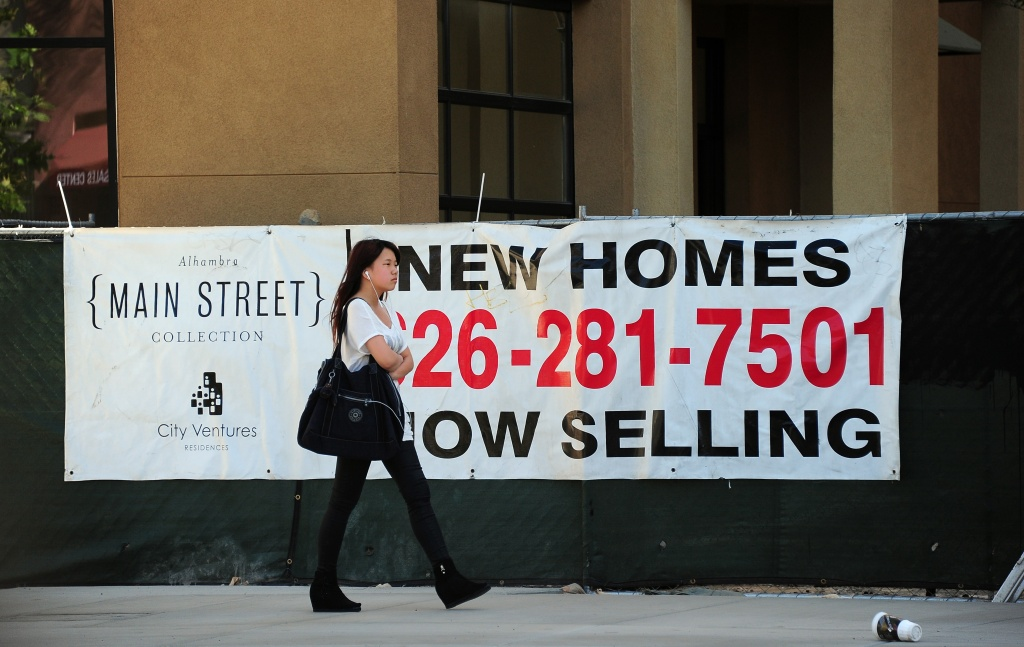 A pedestrian walks past an advertising banner for new home sales in Alhambra, California on September 26, 2013.