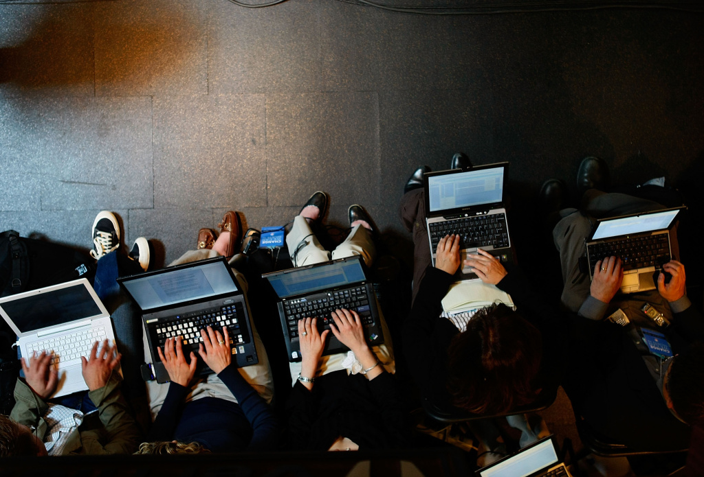 Reporters work on their laptops as Democratic presidential hopeful Sen. Barack Obama (D-IL) speaks during a campaign event at Vernier Software & Technology.