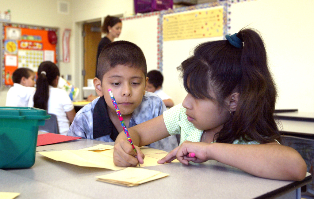 Students work together in teacher Daisy Moran's second-grade bilingual class during summer school at Mozart School July 2, 2003 in Chicago, Illinois.