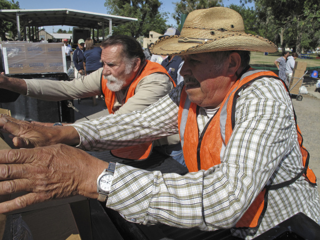 In this June 4, 2015, photo, Fidel Fraga, right, volunteers at a food distribution event in Firebaugh, Calif., serving hundreds of farmworkers out of work because of the state's relentless drought. The food is provided through emergency drought relief funds. Fraga also collected his own box of food because has been laid off for months from his job driving a tractor at a Central Valley farm. Although the drought-assistance package has helped communities across California cope with the driest conditions in recent memory, millions of dollars remain untapped more than one year after it was provided, showing how slowly the wheels of government can turn even in a crisis.