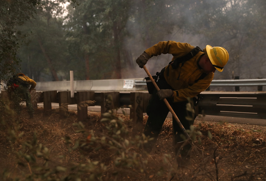 A firefighter clears debris from the side of the road in the Los Padres National Forest on December 8, 2017 near Ojai, California as the Thomas Fire burns.