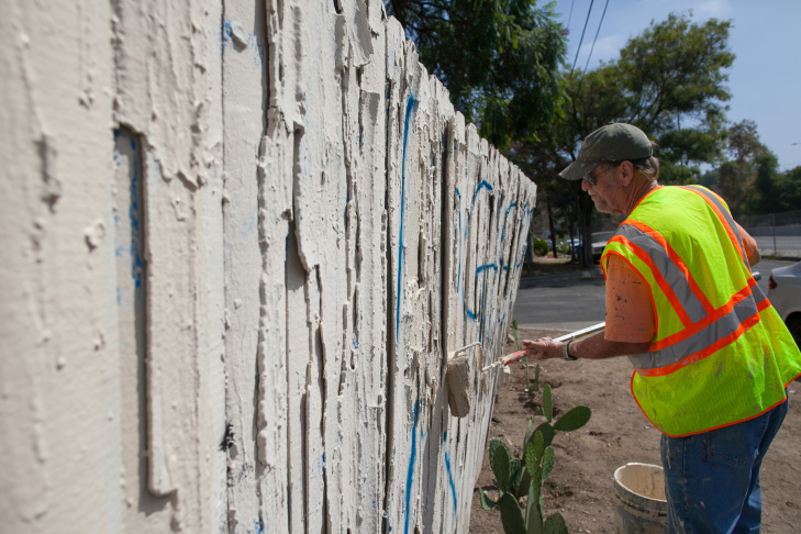 Larry Bender, of Northeast Graffiti Busters, cleans up graffiti on the streets of Highland Park on Tuesday, Aug. 11, 2015.