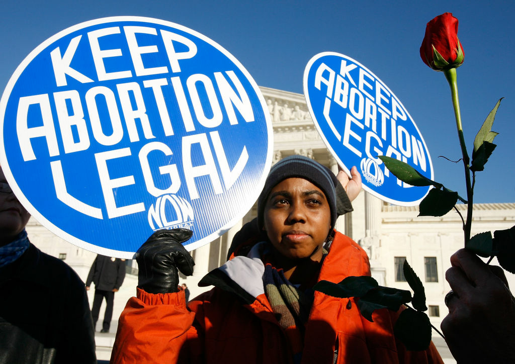 A pro-choice activist holds a sign in front of the U.S. Supreme Court as a pro-life activist holds a rose nearby during the annual