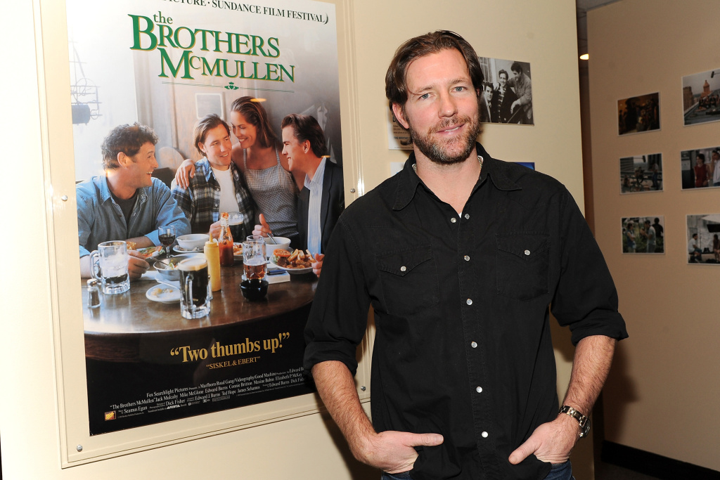Filmmaker Ed Burns poses in front of a poster for his first film