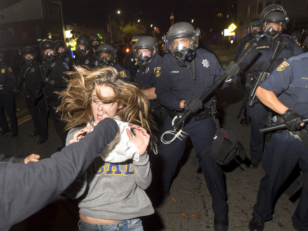 A protester flees as police officers try to disperse a crowd comprised largely of student demonstrators during a protest against police violence in the U.S., in Berkeley, California early Sunday.