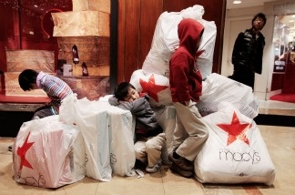 Children wait with shopping bags inside Macy's department store on 'Black Friday,' Nov. 26, 2010 in New York City.