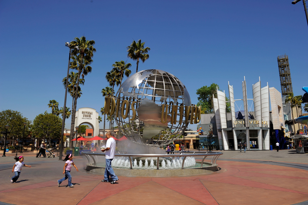 Tourists get their picture taken at the front entrance of Universal Studios Hollywood theme park on May 4, 2010. Comcast has struck a deal with General Electric to take control of all of NBCUniversal.