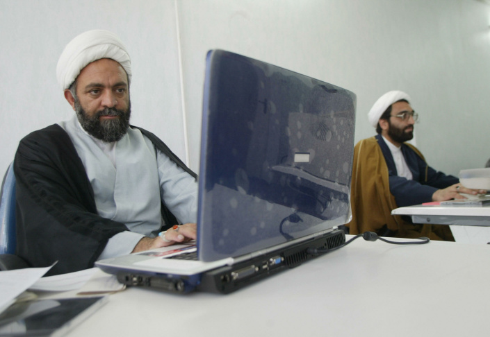 Iranian clergyman Nematollah Daneshmand (L), webmaster for saneei.org -- the site of Grand Ayatollah Yusuf Saanei, works on his laptop at his office in Qom, south of Tehran.