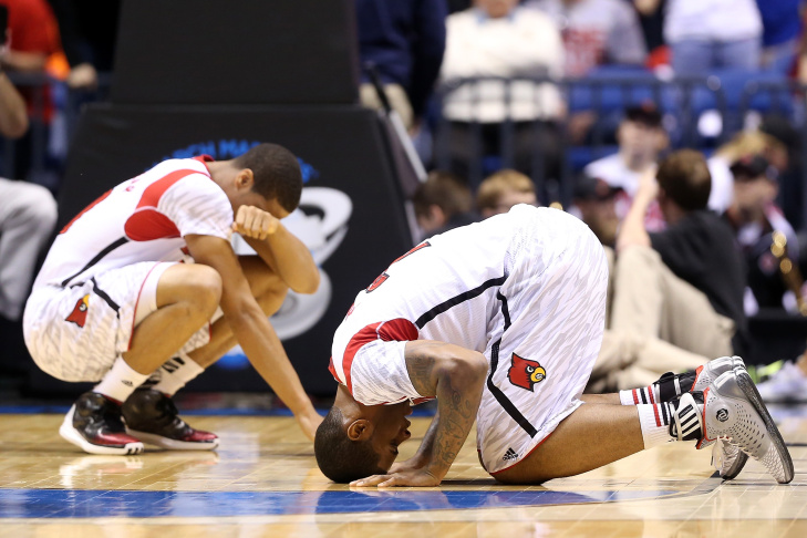 Kevin Ware #5 of the Louisville Cardinals talks with teammate Luke Hancock #11  as Ware is tended to by medical personnel after he injured his leg in the first half against the Duke Blue Devils during the Midwest Regional Final round of the 2013 NCAA Men's Basketball Tournament at Lucas Oil Stadium on March 31, 2013 in Indianapolis, Indiana.