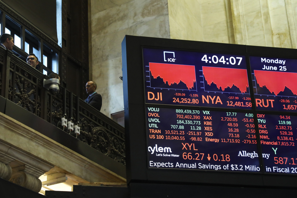 Visitors stand on the upper level next to the day's final numbers following the closing bell at the New York Stock Exchange (NYSE), June 25, 2018 in New York City.