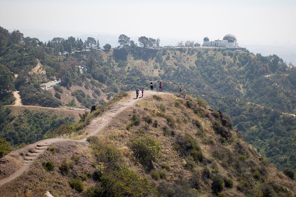 People hike along a ridge overlooking the Griffith Observatory in Griffith Park on March 29, 2015 in Los Angeles, California.