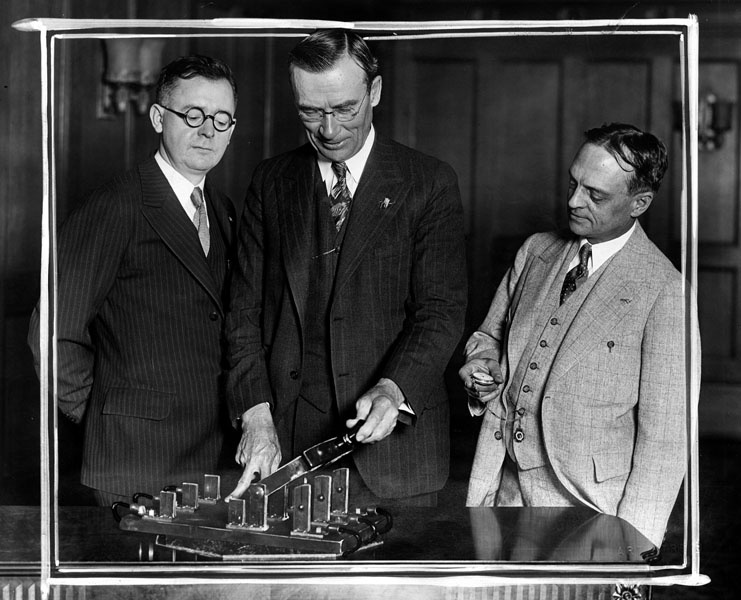 June 1, 1929: Mayor George Cryer about to push the electric switch which will light up green lanterns around LA, symbols of hospitable soda fountain services. L: A.H. Vossmeyer, representing druggists at whose stores the lanterns will be placed. R: A.V. Wainright, President of California Consumers Co., sponsors of the movement, which will revive the spirit of the old inns.
