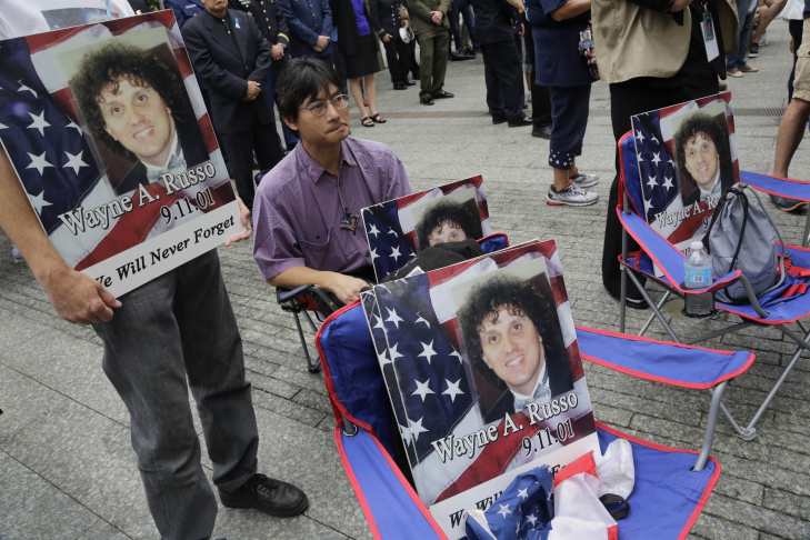 NEW YORK, NY - SEPTEMBER 11: Paola Braut, of Belgium, holds a photograph of her son Patrice along the edge of the North Pool Memorial site during observances at the site of the World Trade Center on September 11, 2014 in New York City. This year marks the 13th anniversary of the September 11th terrorist attacks that killed nearly 3,000 people at the World Trade Center, Pentagon and on Flight 93. (Photo by Justin Lane-Pool/Getty Images)