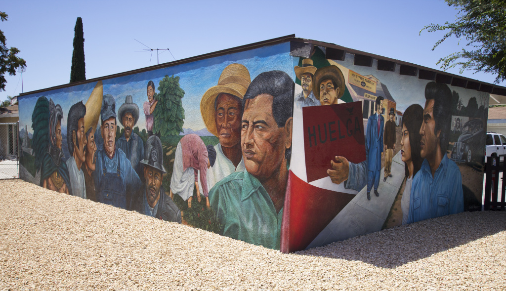 El Proletariado de Aztlán (The Proletariat of Aztlán, 1979) depicts protagonists of the social and cultural movements afoot during Emigdio Vásquez's childhood in Orange County, Calif. The mural, restored in 2014, is located on two sides of a garage in Orange.