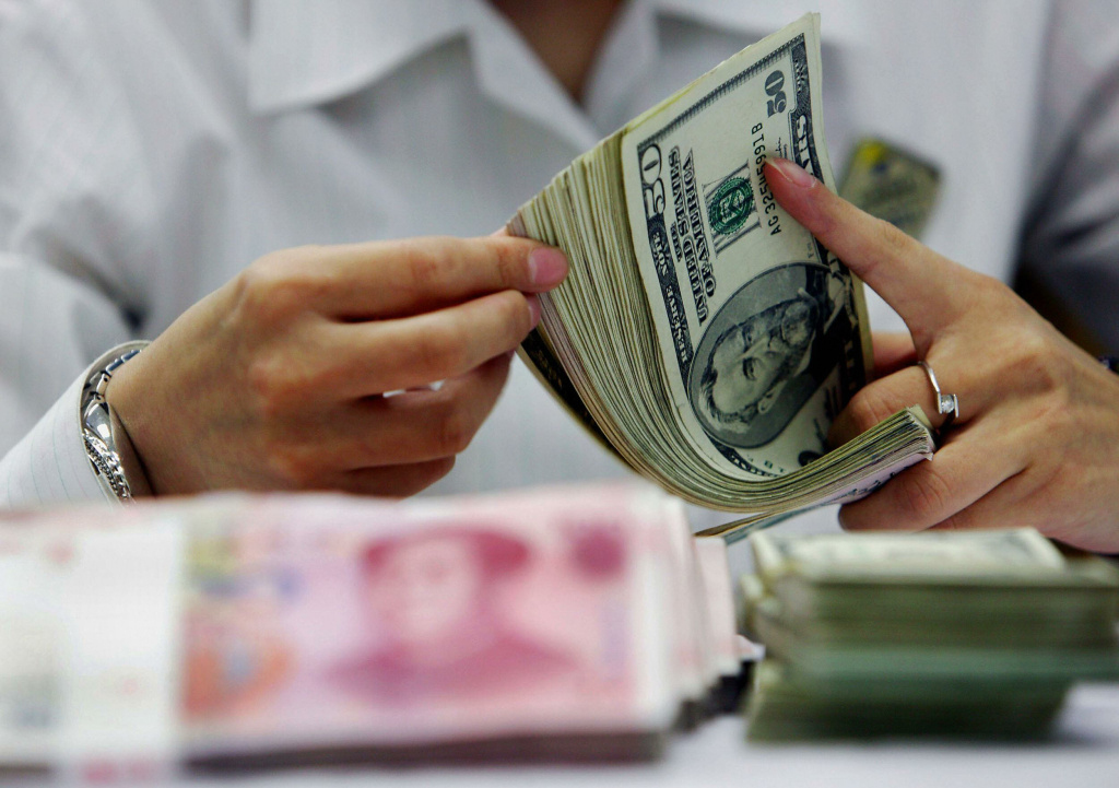 A bank teller counts the stack of Chinese yuan and US dollars at a bank in Shanghai on July 22, 2005.