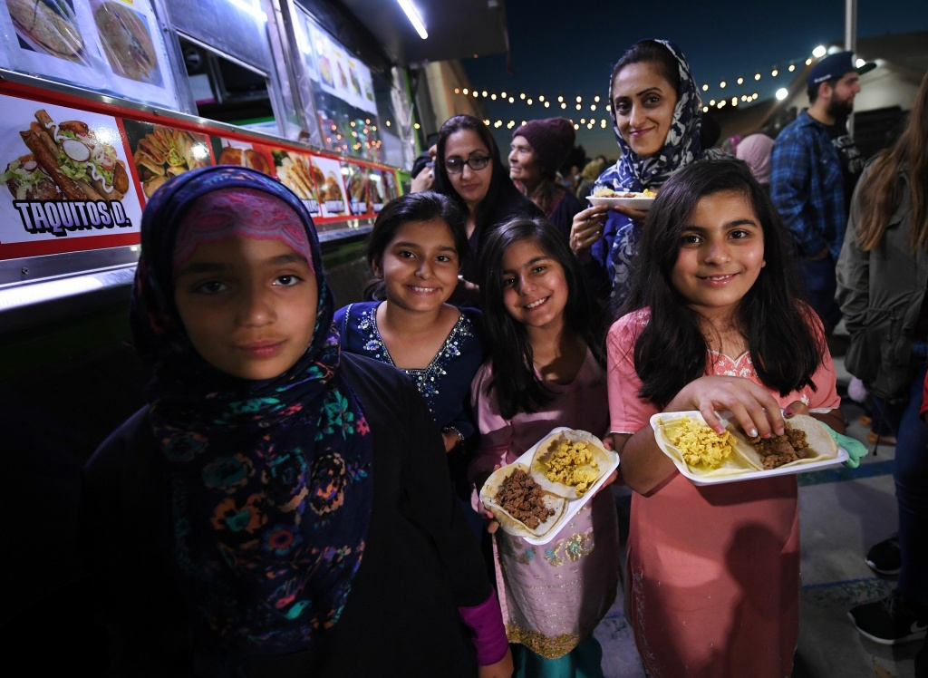 Muslim children break their Ramadan fast after sunset by eating halal Mexican tacos from a food truck, during a campaign called 'Taco Trucks at Every Mosqude' at the Islamic Center in Santa Ana, California on June 14, 2017.