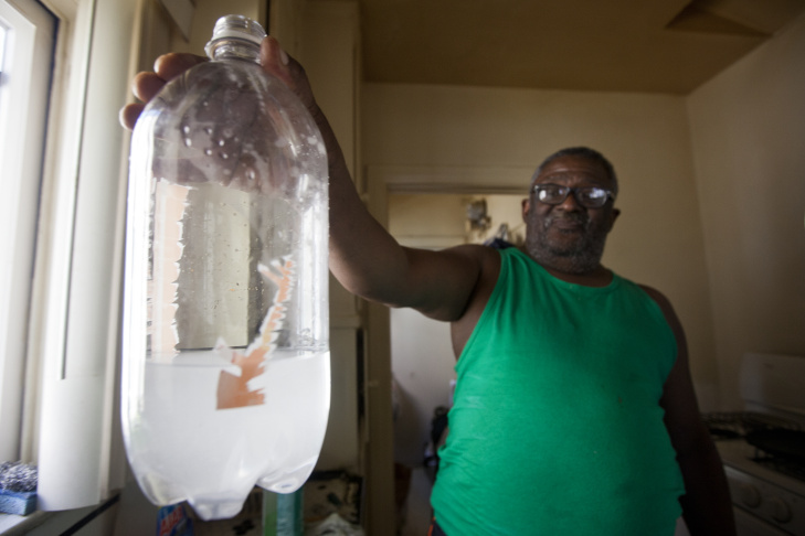 Maywood resident Robert Taylor holds up a bottle filled with tap water from his kitchen sink.
