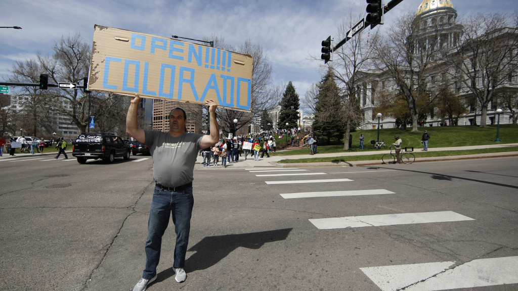 A protester waves a placard during a car protest against the stay-at-home order issued by Colorado Gov. Jared Polis to stem the spread of the new coronavirus on April 19 in Denver.