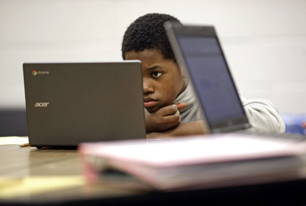 In this Feb. 12, 2015 photo, Marquez Allen, age 12, reads test questions on a laptop computer during a trial run of a new state assessment test linked to the Common Core standards at Annapolis Middle School in Annapolis, Md. California has embraced the Common Core standards, but on Wednesday, March 11, 2015, the state's Board of Education suspended its Academic Performance Index for the 2014-2015 school year in an acknowledgement that teachers and students need more time to adjust to the new computer- and tablet-based tests.