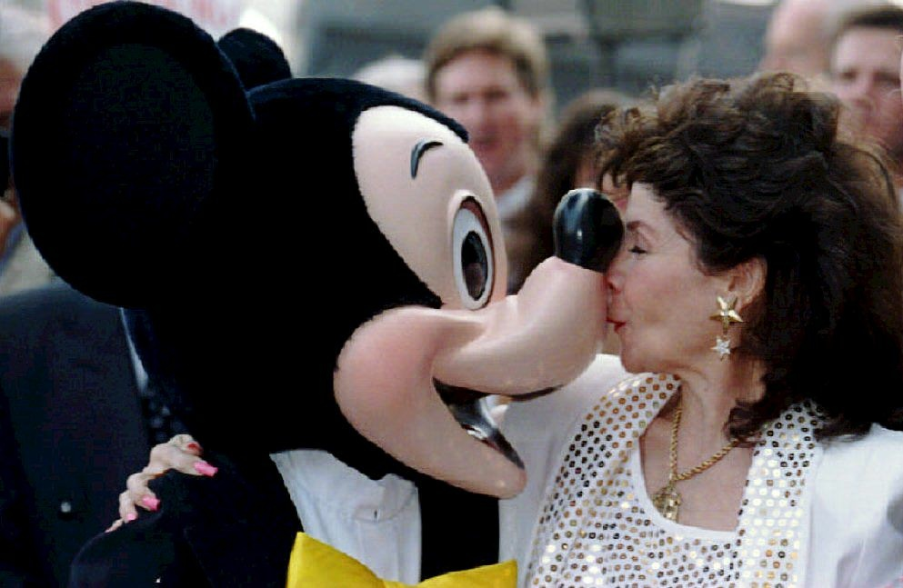 Annette Funicello kisses Mickey Mouse 14 September 1993 after she received a star on the famous Hollywood Walk of Fame in California. The U.S. actress and singer is best known as a famous mouseketeer on the popular 1960's television show, 'The Mickey Mouse Club' as well as the beach movies she made with Frankie Avalon.