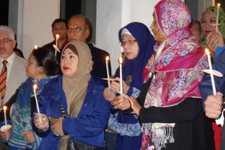Mita Tommy of Reseda, in the blue coat and brown headscarf, joins in a candlelight vigil at the Islamic Center of Los Angeles for victims of the Paris terrorist attacks