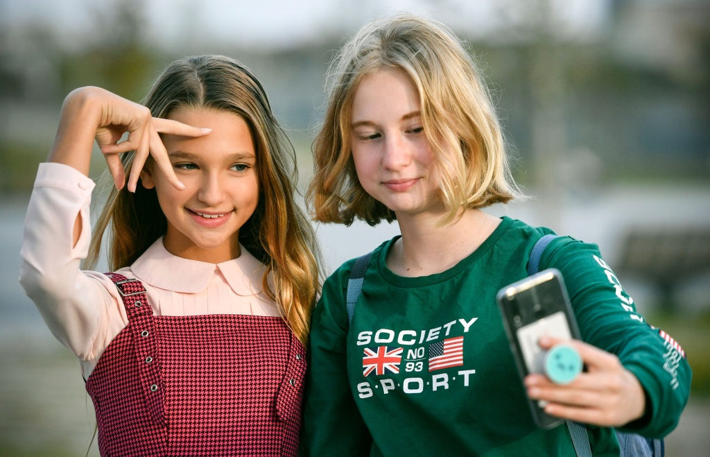 Russian child blogger Liza Anokhina (L), 12, participates in a shoot for her blog in a Moscow park on September 13, 2019.