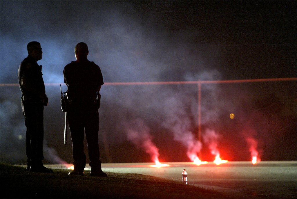 FILE: Bakersfield police officers stand by outside during a murder investigation on July 8, 2003 in Bakersfield, California.