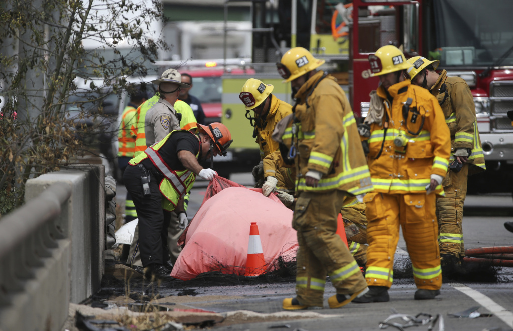 Investigators view a body amid the wreckage after a fiery collision of two big trucks and several smaller vehicles killed one person and injured several others while triggering a massive traffic jam on Interstate 5 just north of downtown Los Angeles Tuesday, April 25, 2017.